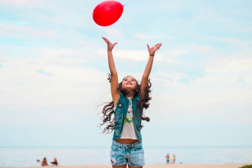 Kind will einen roten Ballon fangen