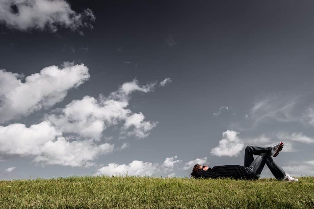 Mann übt den Bodyscan beim Liegen im Grass