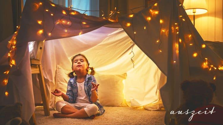 kleines-Mädchen-meditiert-unter-einem-Deckenzelt
