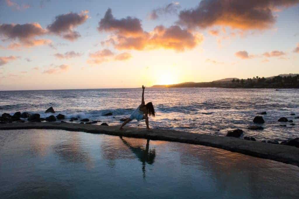 Frau macht Yoga Übung am Strand