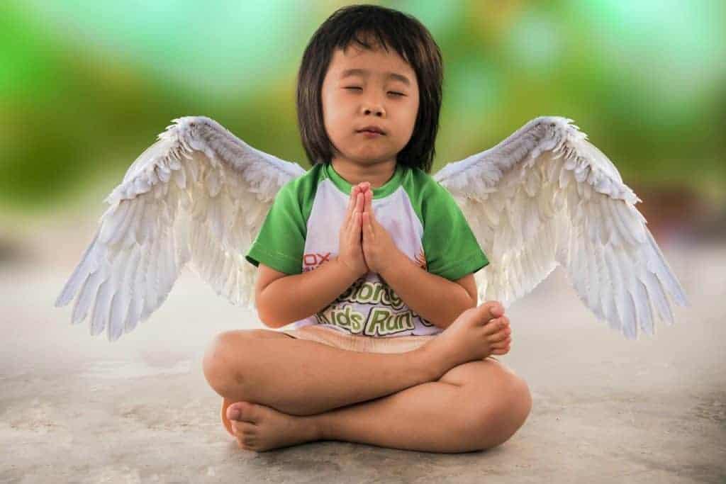 Kind mit Engelsflügel beim meditieren