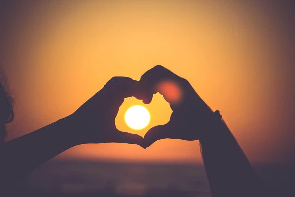 Zwei Hände die ein Herz bilden im Sonnenuntergang