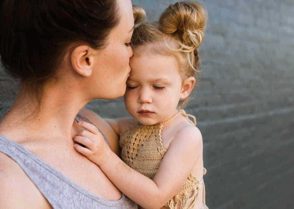 Mutter hält und küsst ihre kleine Tochter