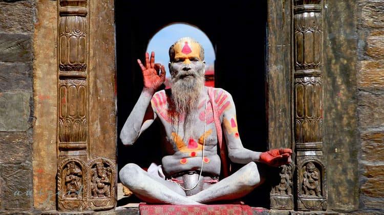 Bunt-bemalter-Yogi-sitzt-auf-einem-Meditationskissen