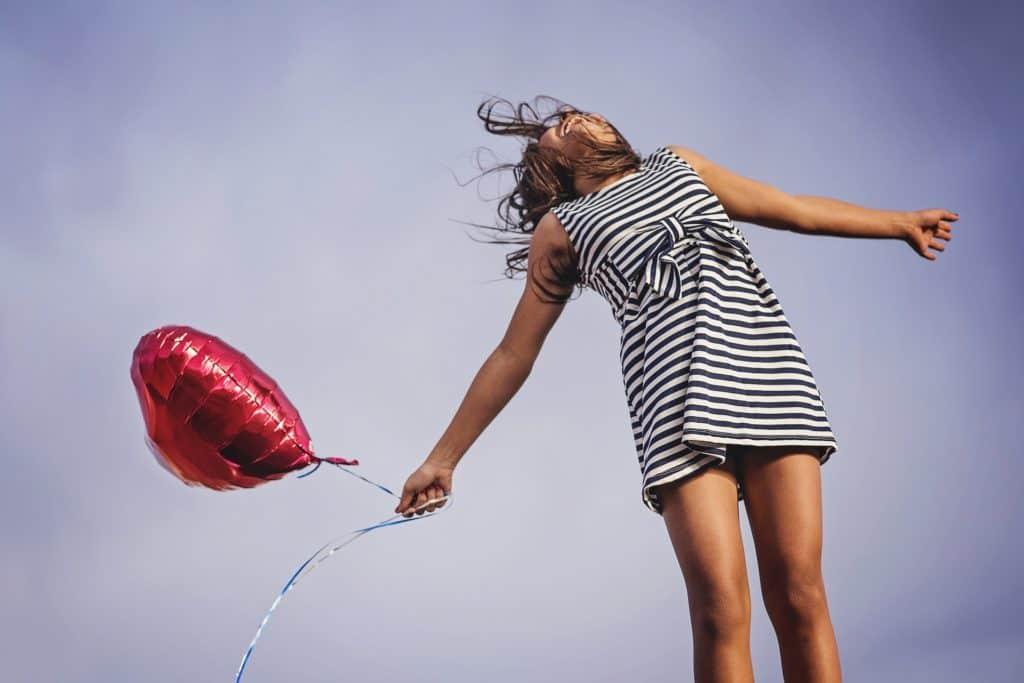 Glückliche Frau hält einen roten Ballon und lacht