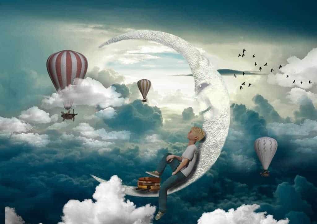 Junge liegt auf dem Halbmond und schwebt über den Wolken