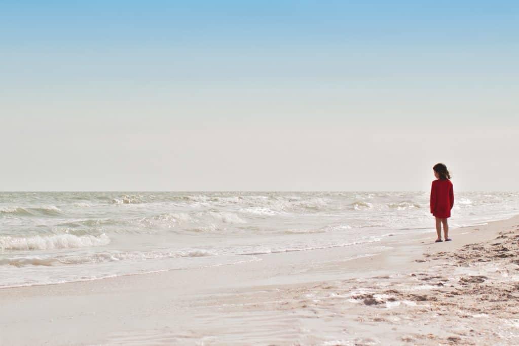 Kind schaut hinaus auf das Meer
