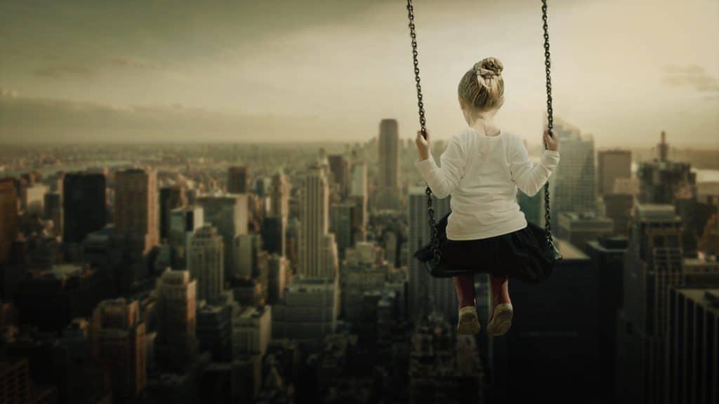 Mädchen in einer Fantasiereise auf einer Schaukel hoch über Wolkenkratzern