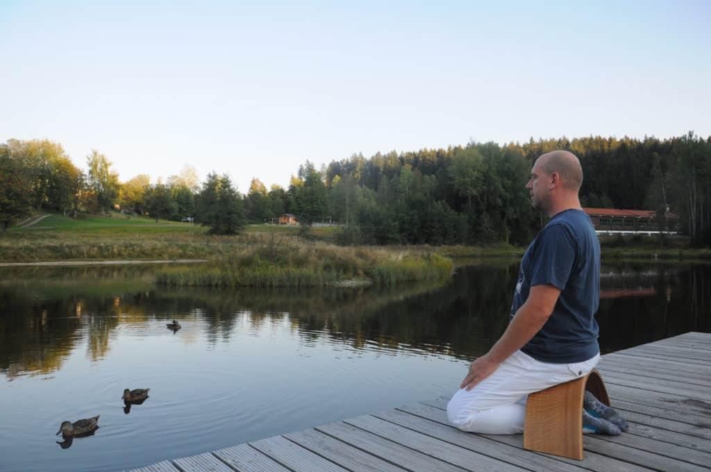 Carsten Warga sitzt auf der Ombow Meditationsbank am See