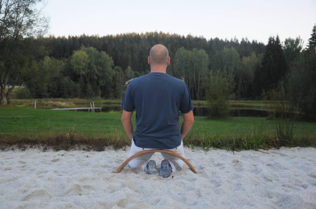 Carsten sitzt mit dem Rücken zum Bild auf der Ombow Meditationsbank im Sand