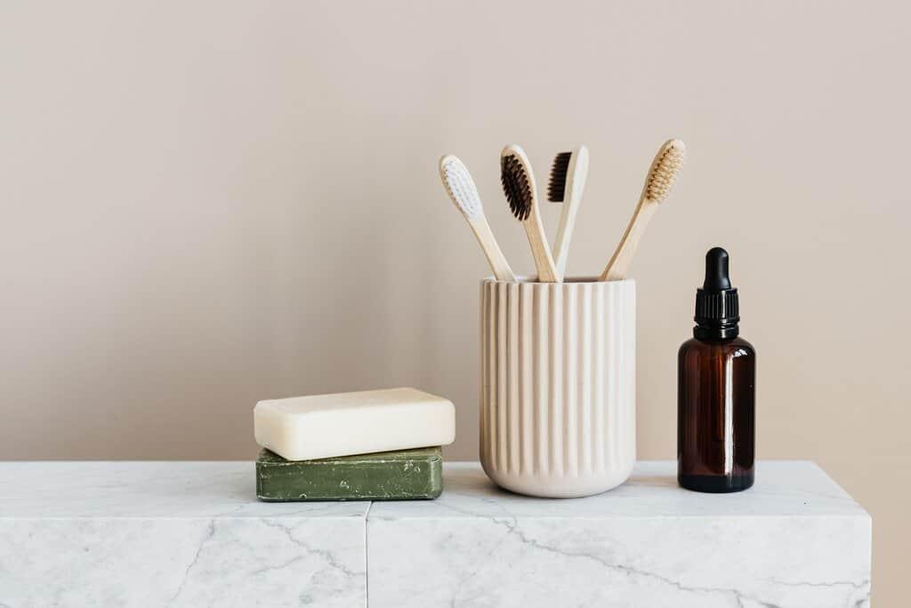 Zahnbürsten und Seifen auf einem Regal im Bad