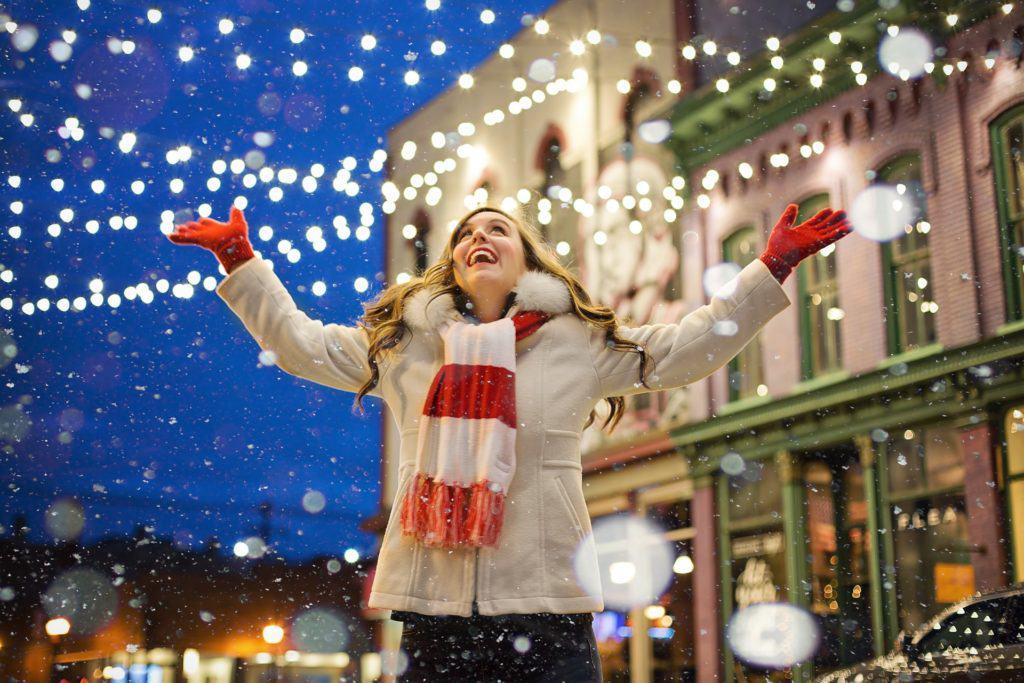 Glückliche Frau unter Weihnachtsbeleuchtung