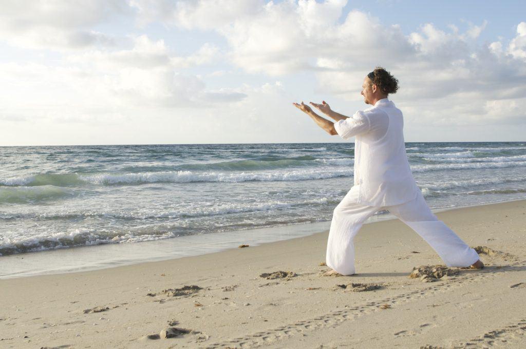 Tai Qi Übungen am Strand um das Wurzelchakra auszugleichen