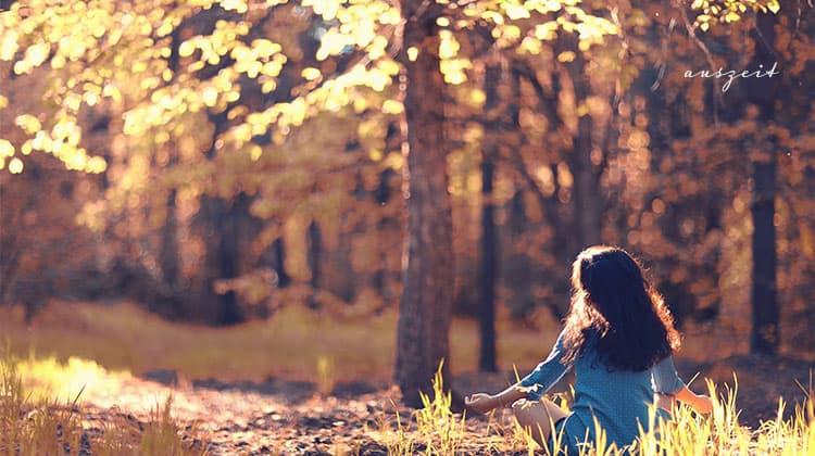 Frau-meditiert-im-Sonnenschein-im-Wald