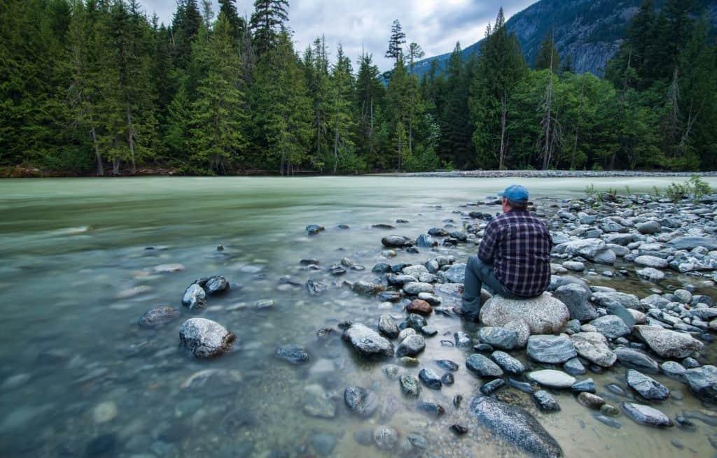 Mann sitzt an einem Fluss  im Wald