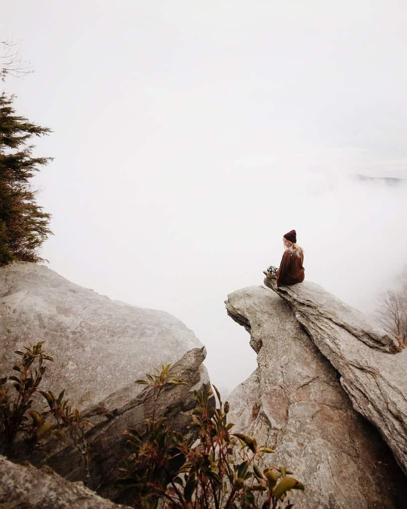 Bild von einer meditierenden Frau in den Bergen über den Wolken