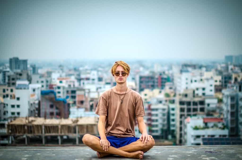 Bilder von Meditierenden auf einem Hausdach ueber der Stadt